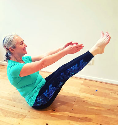 Cardiff Yoga teacher Amanda Powell (Anjali) demonstrates the yoga posture navasana or boat pose