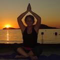 Cardiff Yoga teacher Amanda Powell (Anjali) with hands in anjali mudra on a beach at sunset in Lemnos Greece